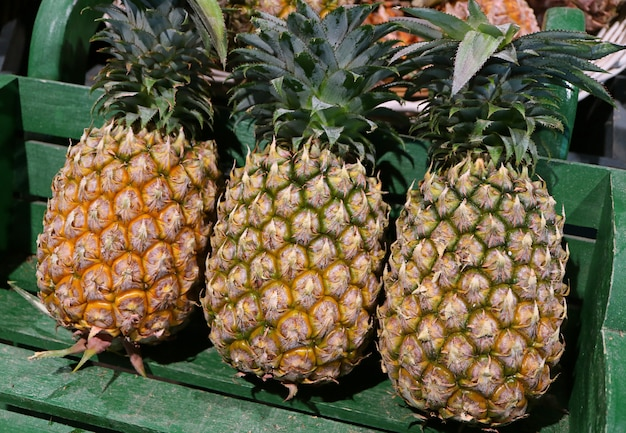Três frutos maduros abacaxi inteiro com haste verde em uma cesta de madeira, tailândia