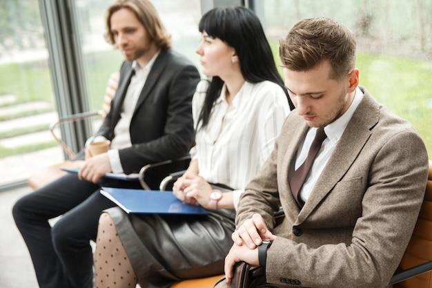 Três funcionários de escritório estão esperando por um compromisso