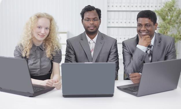 Três funcionários sentados no local de trabalho no escritório