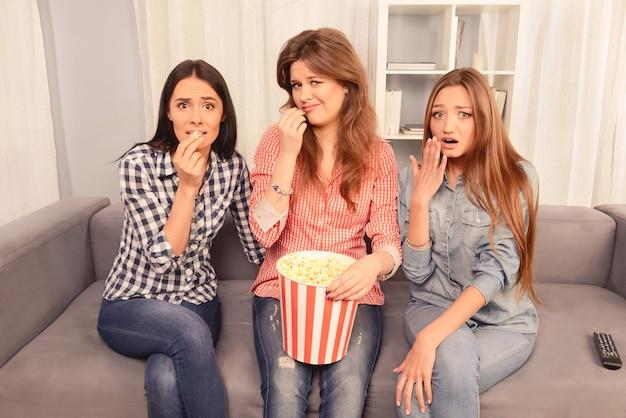 Três garotas assustadas assistindo filme e comendo pipoca