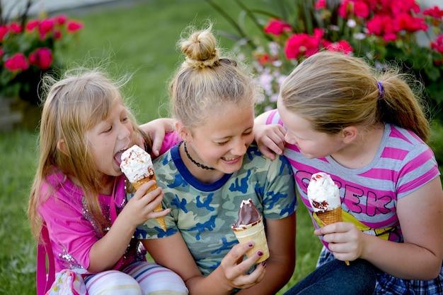 Três garotas atraentes e felizes comendo sorvete em xícaras de waffle