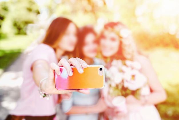 Três garotas bonitas fazendo selfie com a noiva no casamento