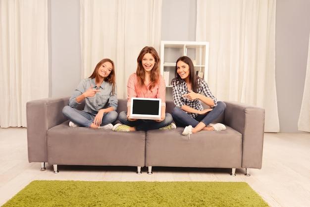 Três garotas bonitas sentadas no sofá e apontando na tela preta do laptop