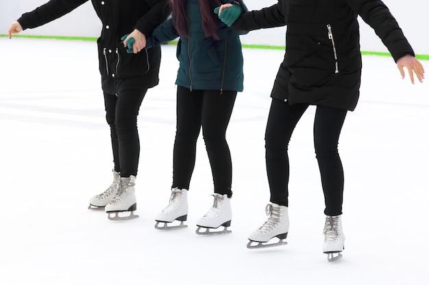 Três garotas de mãos dadas, patinando no gelo na pista de gelo. esportes, hobbies e recreação de pessoas ativas