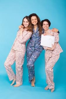 Três garotas de pijama colorido se divertindo no azul
