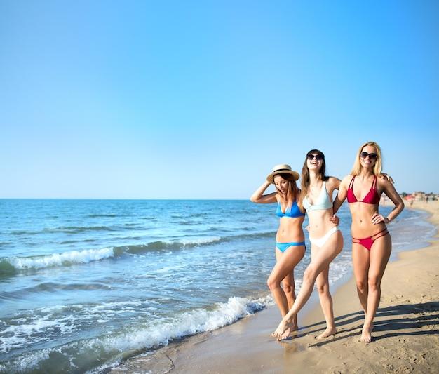 Três garotas divertidas de maiô na praia