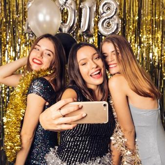 Três garotas do partido levando selfie na celebração do ano novo