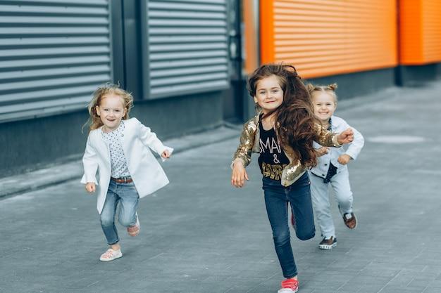 Três garotas engraçadas felizes correndo pela rua
