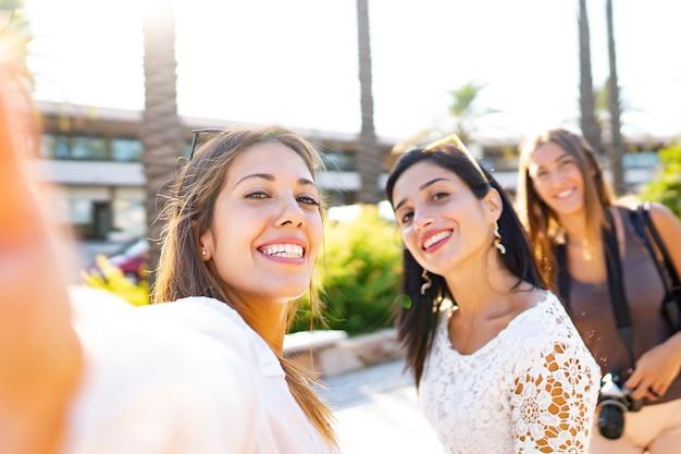 Três garotas felizes de férias tirando selfies na cidade sorrindo lindas moças se divertindo com tecnologia e fotografia ao ar livre na cidade aproveitando o destino da viagem