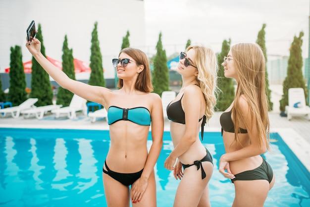 Três garotas felizes em trajes de banho e óculos escuros fazem selfie perto da piscina. férias no resort. mulheres bronzeadas nas férias de verão