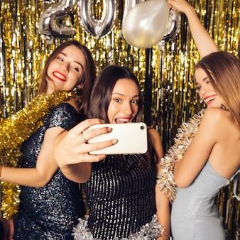 Três garotas felizes levando o selfie na celebração do ano novo