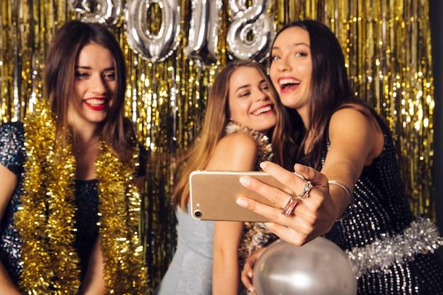 Três garotas levando selfie na celebração do ano novo