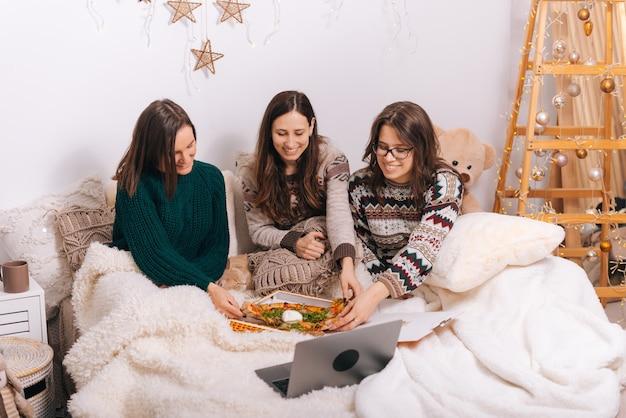 Três garotas maravilhosas estão desfrutando de pizza entregue em uma noite de cinema.