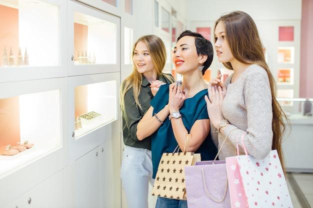 Três garotas olhando vitrine em compras no shopping