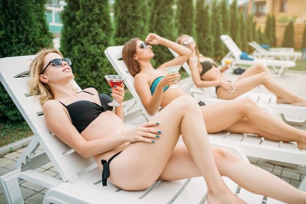 Três garotas relaxam e tomam banho de sol nas espreguiçadeiras, no verão. jovens mulheres sexy nas férias de verão