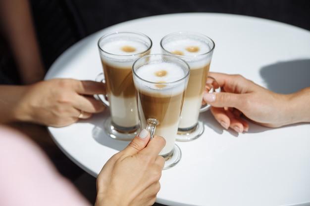 Três garotas segurando um copo de café com leite perfumado nas mãos