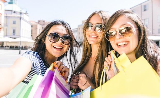 Três garotas tomando selfie e fazendo compras
