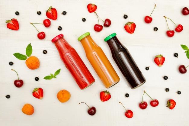 Três garrafas com suco, frutas em branco de madeira