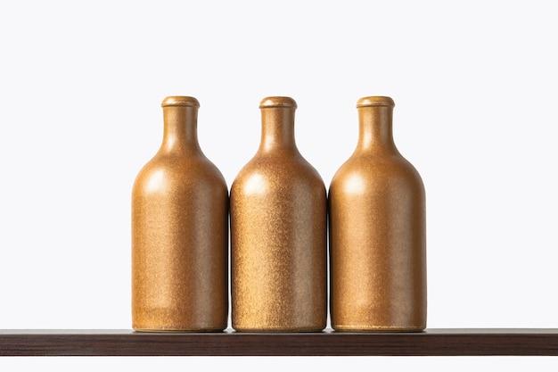 Três garrafas de cerâmica estão em uma prateleira de madeira o