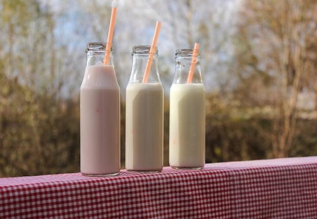Três garrafas de milk-shake na mesa de madeira ao lado da vista para o rio