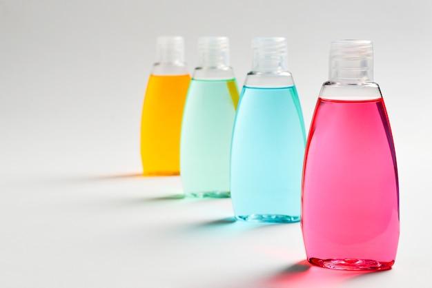 Três garrafas de plástico com sabonete líquido amarelo, verde e vermelho.