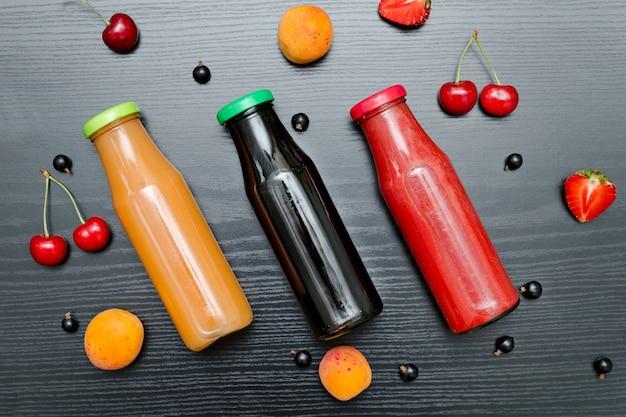 Três garrafas de suco e frutas.