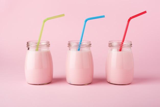 Três garrafas de vidro de iogurte de frutas com canudos coloridos sobre fundo rosa pastel