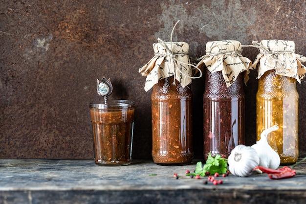 Três garrafas de vidro de molho tkemali georgiano sortido com ingredientes na mesa de madeira rústica. copie o espaço