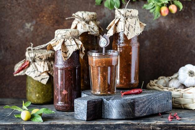Três garrafas de vidro de molho tkemali georgiano sortido com ingredientes na mesa de madeira rústica.