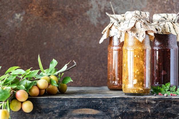 Três garrafas de vidro de molho tkemali georgiano variado com ingredientes em uma mesa de madeira rústica