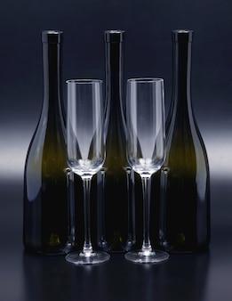Três garrafas de vinho e duas taças de vinho vazias