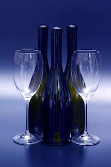 Três garrafas de vinho vazias e duas taças de vinho vazias