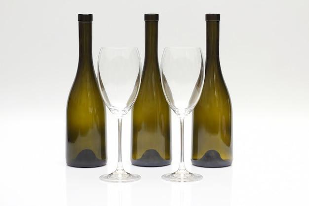 Três garrafas de vinho vazias viradas para cima e dois copos em um branco