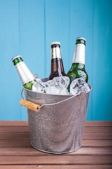 Três garrafas fechadas de cerveja dentro de um balde de metal cheio de gelo