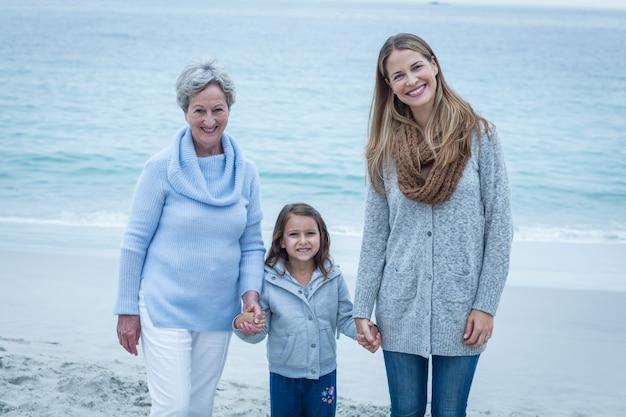 Três gerações de mulheres em pé na praia