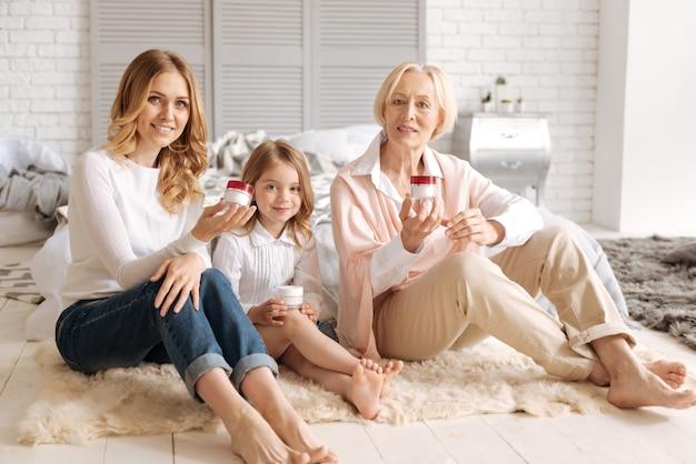 Três gerações de mulheres em uma família extensa, sentadas em uma linha em um tapete e segurando potes de creme.