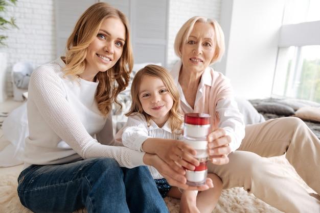 Três gerações de mulheres encantadoras sentadas no tapete, colocando potes de creme umas nas outras e parecendo divertidas com o processo