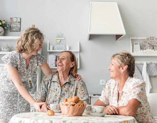Três gerações de mulheres tomando café da manhã na cozinha
