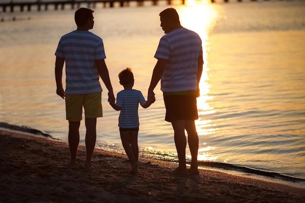 Três gerações masculinas pelo mar ao pôr do sol