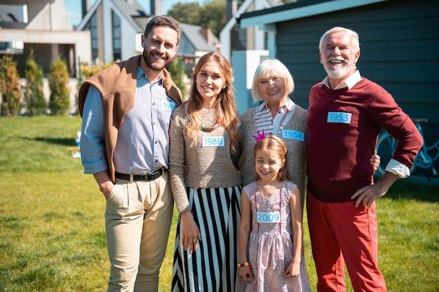 Três gerações. menina alegre com um sorriso no rosto enquanto está perto da avó