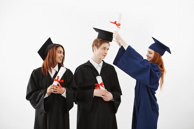 Três graduados alegres que sorriem falando enganando guardando diplomas.