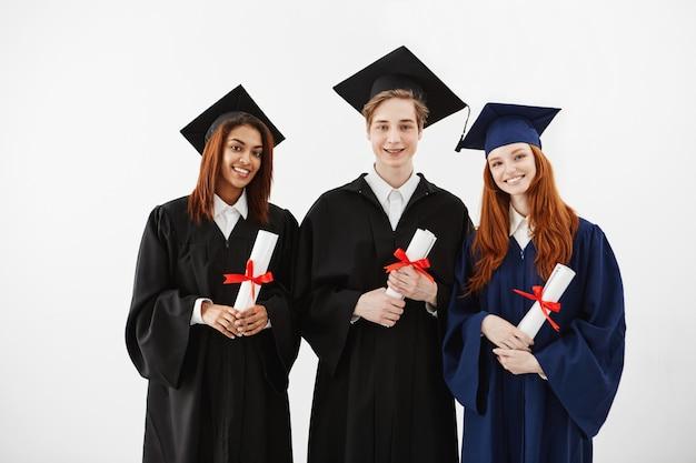 Três graduados felizes sorrindo segurando diplomas.