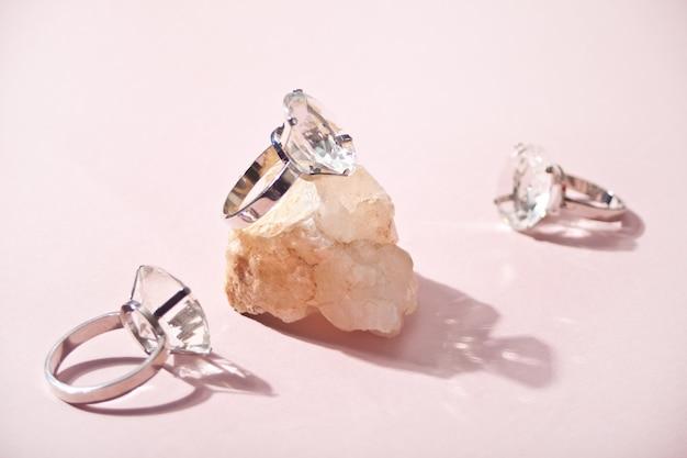Três grandes anéis de diamante e um pedaço de pedra com sombra dura.