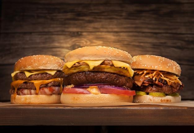 Três grandes hambúrgueres em fundo de madeira. vista frontal de baixo ângulo. copie o espaço para seu texto.