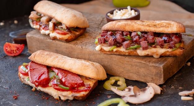 Três grandes porções sanduíches de baguete com alimentos misturados.