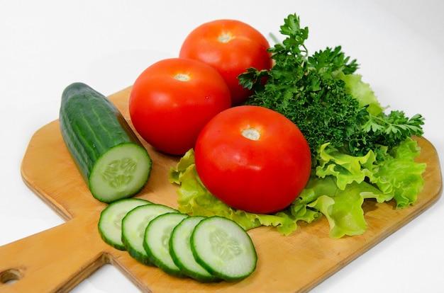 Três grandes tomates verdes pepino picado anel placa de madeira conceito de comida saudável vegetarianismo, dieta ceto, dieta paleo.