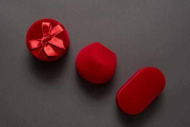 Três guarda-joias fechados vermelhas em um fundo preto.
