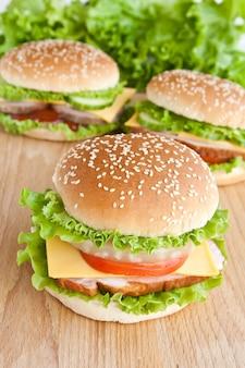 Três hambúrguer com carne e legumes na chapa de madeira