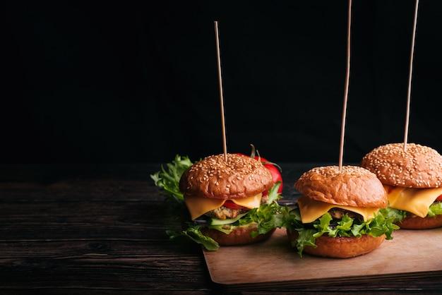 Três hambúrgueres caseiros com carne, queijo, alface, tomate em uma placa de madeira sobre uma mesa em um fundo preto