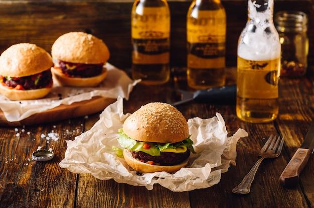Três hambúrgueres com garrafas de cerveja lager.